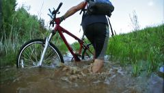 Young sportsman carries a bicycle in hands through a small dirty puddle Stock Footage