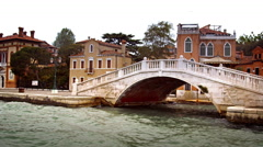 Tracking shot of bridge, boat, and buildings along a canal in Venice. Stock Footage