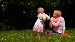 Mother and daughter blowing bubbles Stock Footage