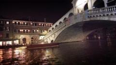 Stock Video Footage of A single motor boat travels underneath the Rialto Bridge