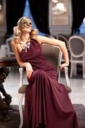 Sensual blonde with a mask, sitting in a ballroom - stock photo