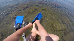 1st person POV of diver with snorkeling gear putting on swim fins in the surf Stock Footage