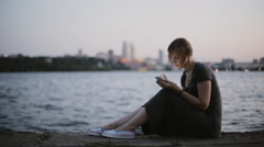 Woman Shopping In The Online Store Sitting On The City Waterfront - stock footage