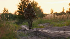 Armed man in camouflage goes towards sunset - stock footage