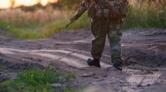 Armed man in camouflage walking along the road Stock Footage