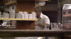 Static shot of a man working in the back of an Italian cafe. Stock Footage