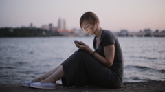 Girl sitting in the evening on the waterfront gaining a friend Stock Footage