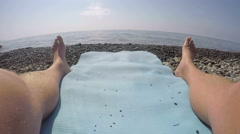 1st person POV of man relaxing on the beach mat looking towards the sea Stock Footage