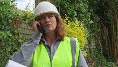 Attractive redheaded female architect / engineer speaks on cell phone Stock Footage