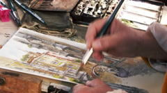 Shot of artist painting with watercolors a scene of a gondola on a canal in Stock Footage