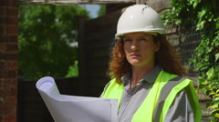 Attractive red-headed female architect / engineer looks at plans then smiles - stock footage