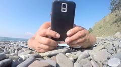 Male traveler holding smart phone in hands lying on the beach close up - stock footage