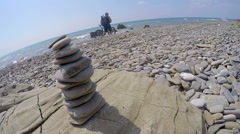 Pyramid of pebbles on empty wild beach male traveler pushing bike along the surf Stock Footage