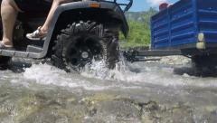 ATV quadbike with trailer crossing creek Uskut, Crimea - stock footage