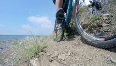 Slow motion of traveler riding mountain bike on trail along rocky wild beach Stock Footage