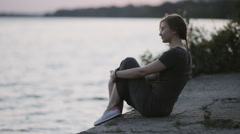Young girl holding a warm summer evening on the river bank Stock Footage