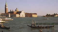 Shot of several gondolas and a vaporetto in the canal with the island of San Stock Footage