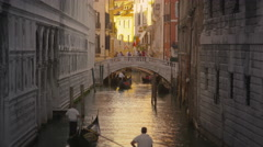 Shot of several gondolas in a canal with a bridge. Stock Footage