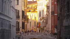 Gondoliers pass underneath a pedestrian bridge on a sunlit canal Stock Footage