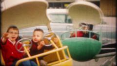 2320 - children enjoy rides at the amusement park - vintage film home movie Stock Footage