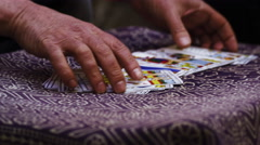 Close-up footage of two pairs of hands shuffling and adjusting tarot cards - stock footage