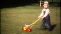 2329 - little boy cuts the grass with his lawn mower - vintage film home movie Stock Footage