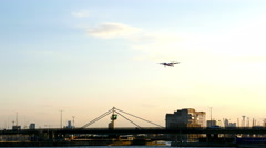 Airplane is landing on City Airport London, bridge with vehicules on background Stock Footage