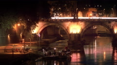 Left-to-right pan of illuminated Ponte Sant'Angelo at night Stock Footage