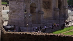 Tourists stroll by the base of the Arch of Constantine Stock Footage