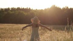 Young girl with arms outstretched feeling freedom in grass field  HD Stock Footage