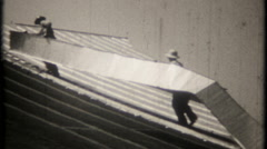 2334 - workers install sheet metal roof on building - vintage film home movie Stock Footage