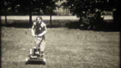 2336 - pretty woman cuts the grass with lawn mower - vintage film home movie Stock Footage