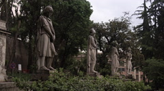 Single Roman statues in a green garden - stock footage