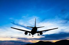 Silhouetted commercial airplane flying at sunset Stock Photos
