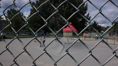 Stock Video Footage of POV Through Chain Link Fence of Skateboarders
