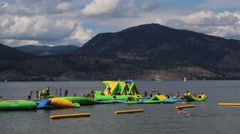 Families at Play on Inflatable Water Park - stock footage