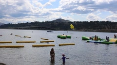 Swimmers in Foreground and Couple Parasailing in the Background Stock Footage