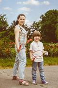 Portrait of small boy in park holding a racquet for badminton smiling, and his Stock Photos