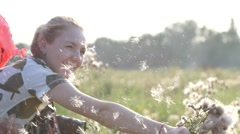 Girl cheerfully play with white cottony furry flowers on sunset nature light  Stock Footage