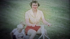 NEW HAVEN, CONN. USA - 1957: Mom on new riding lawn mower towing kids on back. Stock Footage