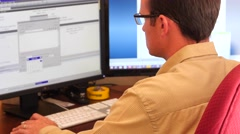 A male working on the computer in his office Stock Footage