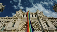 Rainbow flag in Madrid city hall with blue sky and clouds Stock Footage