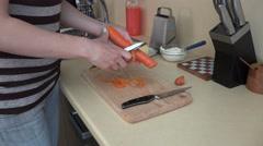 Housewife woman peeling orange carrot with peeler tool. 4K Stock Footage