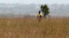 African woman walking through a field. Stock Footage