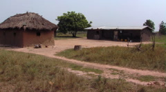 A building and a grassy hut in Africa. - stock footage