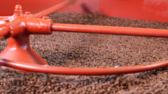 Close up roasted coffee beans being turned & stirred in industrial machine Stock Footage