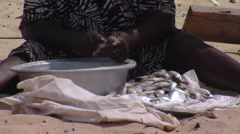 Woman cleaning fish in a bowl in Africa. Stock Footage
