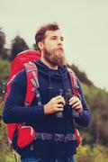 Man with backpack and binocular outdoors Stock Photos