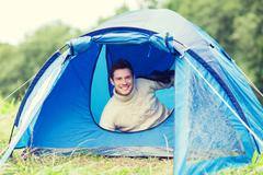 smiling male tourist in tent - stock photo