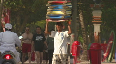 Boy carrying boards on his head in Bali. Stock Footage